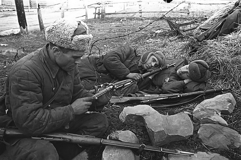 Красноармеец на привале чистит затвор винтовки Мосина