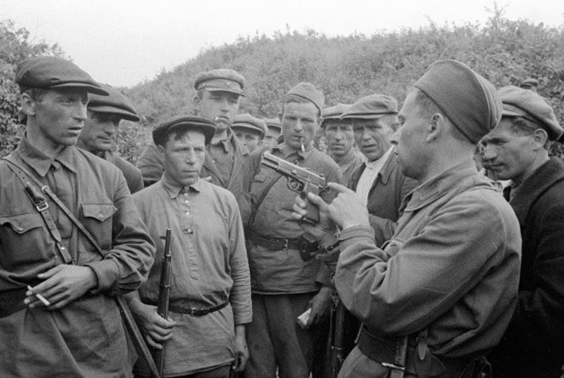 Командир партизанского отряда знакомит бойцов с трофейным оружием
