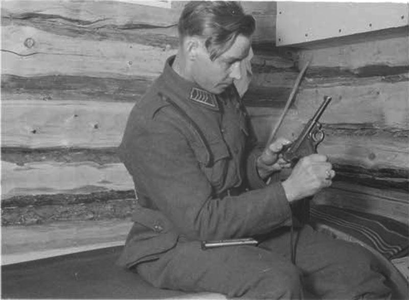 Финский солдат осматривает пистолет Р.08