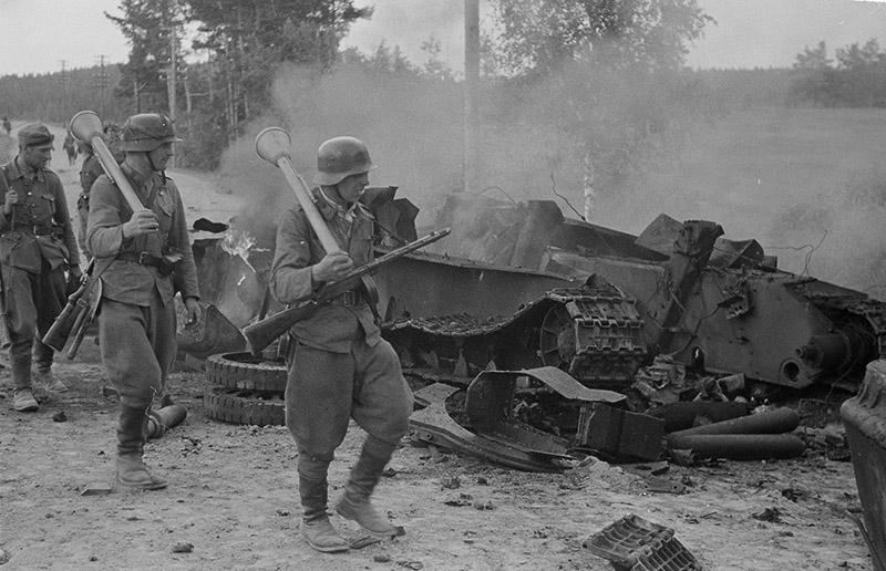 Финские солдаты проходят мимо разрушенного взрывом советского танка Т-34, июнь-июль 1944 года