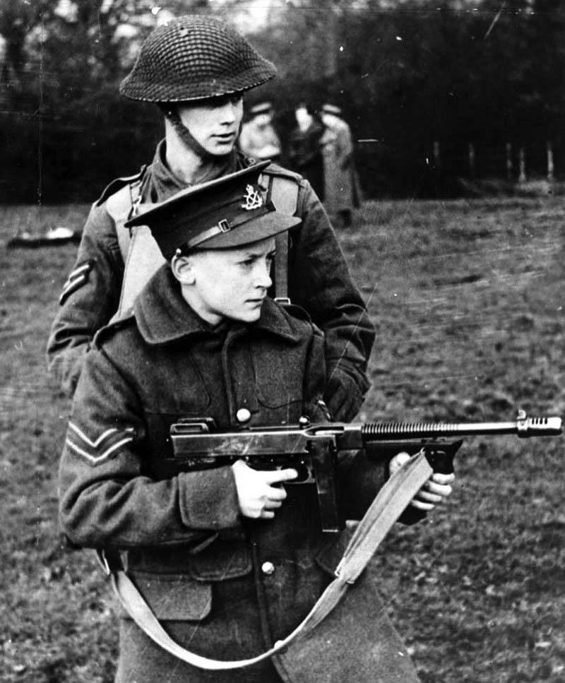 Обучение учащихся одной из английских школ владению стрелковым оружием, у мальчика в руках Thompson M1921A