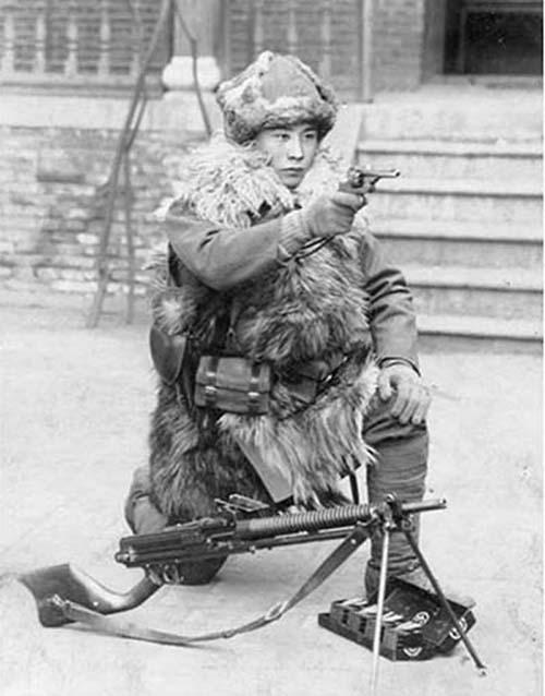 Японский солдат позирует с револьвером Тип 26