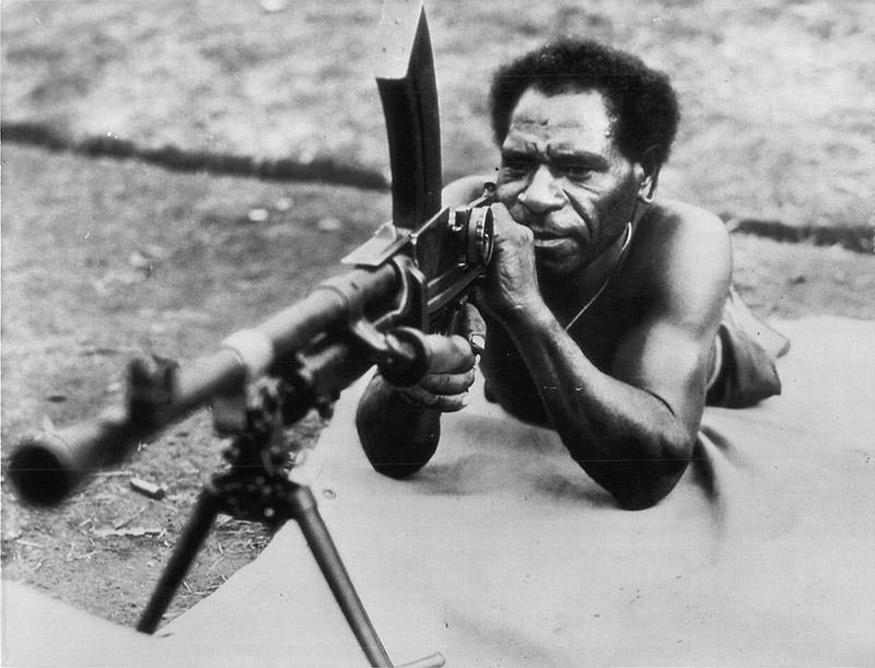 Представитель коренного населения Папуа Новой Гвинеи на учебных стрельбах в тренировочном лагере