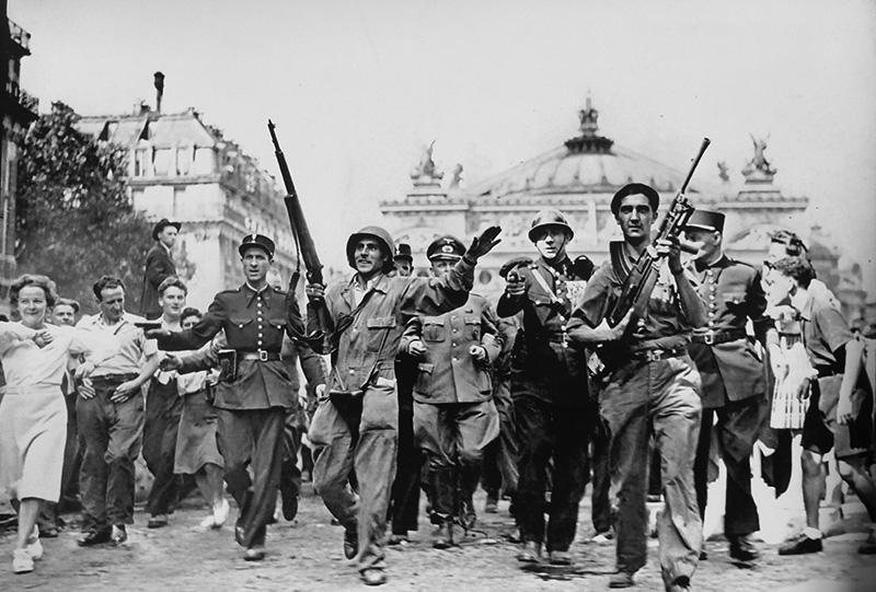 Французские борцы Сопротивления и полицейские конвоируют в сопровождении горожан немецкого пленного офицера