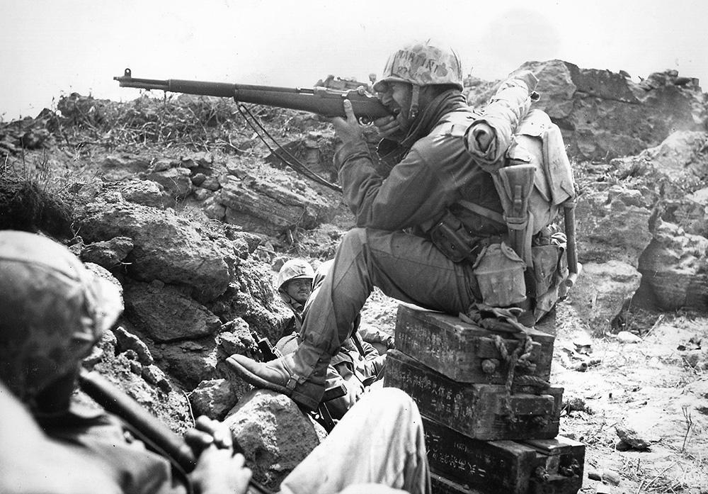 Американский морской пехотинец прицеливается из винтовки M1 Garand во время боев на Иводзиме