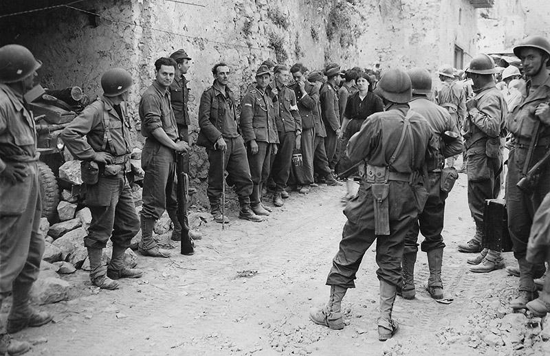 Солдаты 5-й армии сил «Свободной Франции» с немецкими пленными на улице итальянского городка