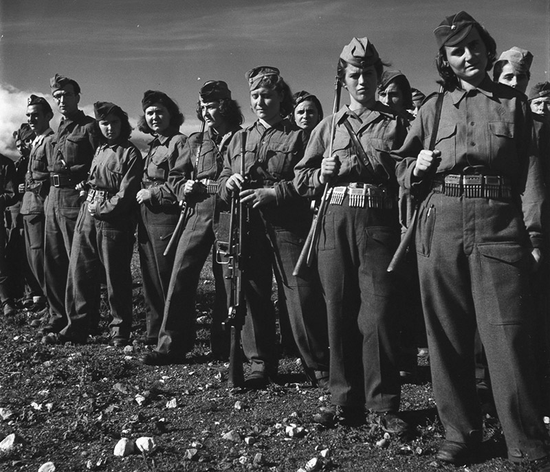 Греческие партизаны в строю. Девушки вооружены трофейными итальянскими винтовками, третья девушка справа — 6,5-мм итальянским пулеметом Breda modello 30