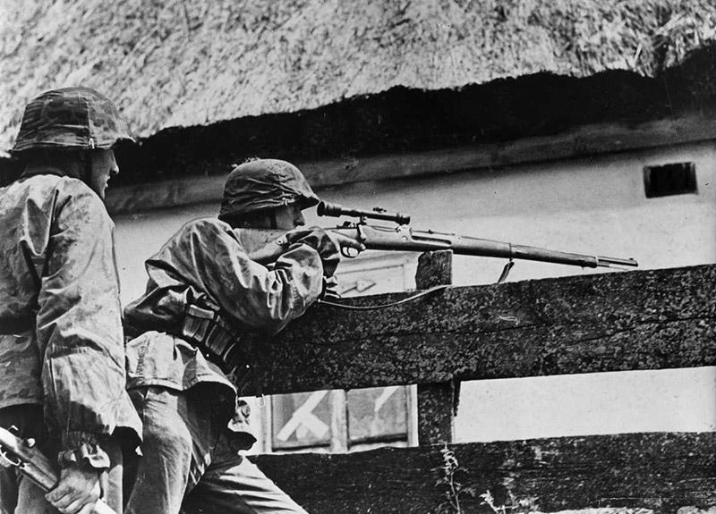 Снайпер войск СС ведет наблюдение через <a href='https://arsenal-info.ru/b/book/2362237253/11' target='_self'>прицел снайперской</a> винтовки на Восточном фронте.