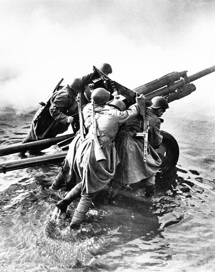 Расчет 76,2-мм дивизионной пушки ЗиС-3 выкатывает своё орудие на позицию для стрельбы. Германия, декабрь 1944 г.