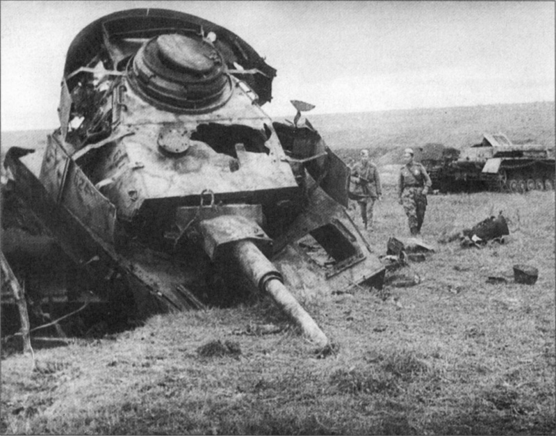 Советские бойцы рассматривают разбитый немецкий танк Pz.Kpfw. IV Ausf. Н (одностворчатый люк и отсутствие на башне трехствольных гранатометов). Танк окрашен в трехцветный камуфляж. Орловско-Курское направление.