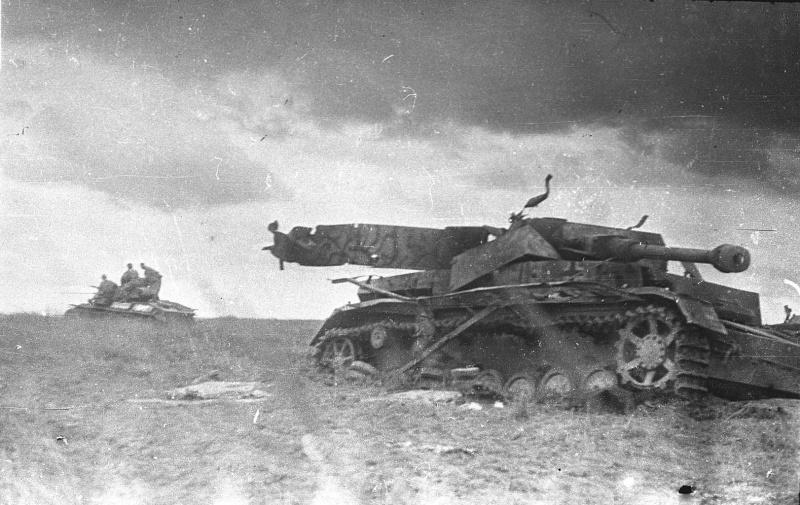 Уничтоженный немецкий средний танк Pz.Kpfw. IV на Курской дуге. На заднем плане удаляющийся советский легкий танк Т-70 с солдатами.