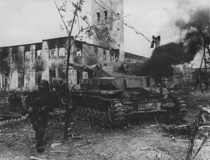 Советские солдаты передвигаются мимо дымящегося немецкого танка Pz.Kpfw. IV. в поселке Красноармейск (сейчас район Волгограда), около сталинградской судоверфи (завод № 264). Здание на фото — пожарная часть около проходной завода.