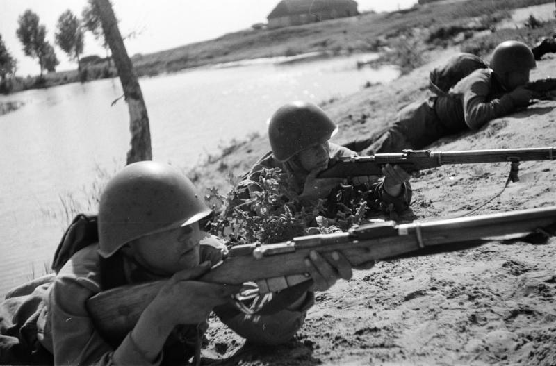 Красноармейцы с винтовками Мосина занимают огневую позицию после переправы через реку.