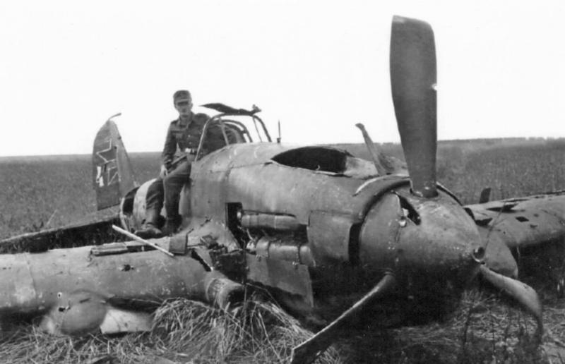 Немецкий солдат фотографируется на разбитом советском штурмовике Ил-2, совершившем вынужденную посадку