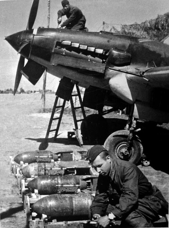 Механик по вооружению гвардии сержант 15-го гвардейского штурмового авиаполка К.Угодин готовит бомбовый груз самолету Ил-2.