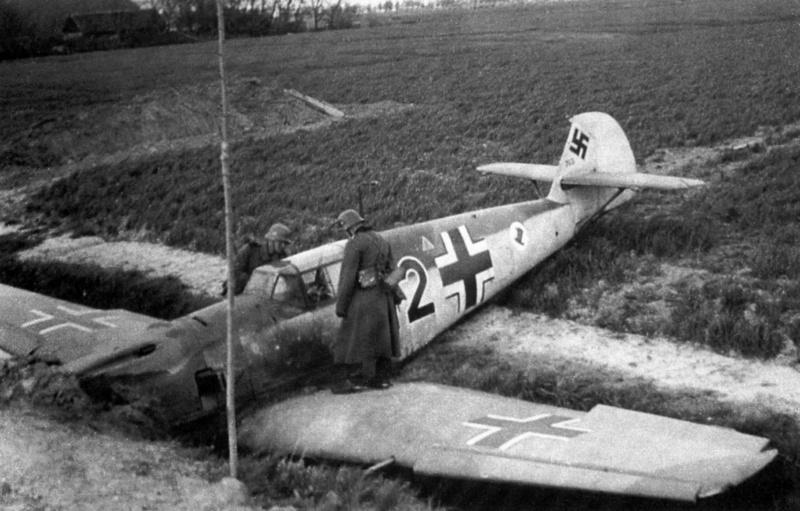 Два немецких солдата осматривают совершивший аварийную посадку истребитель Мессершмитт Bf.109 (Messerschmitt Bf.109E-3)