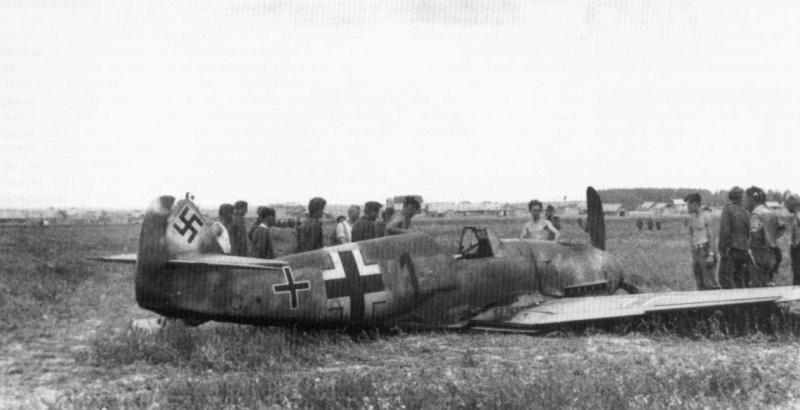 Немецкие военнослужащие у совершившего аварийную посадку истребителя Мессершмитт Bf.109 (Messerschmitt Bf.109F-2)