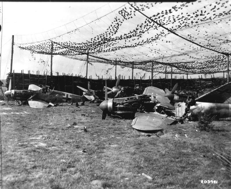 Американский военнослужащий осматривает разбитые и брошенные немецкие истребители Messerschmitt Bf.109