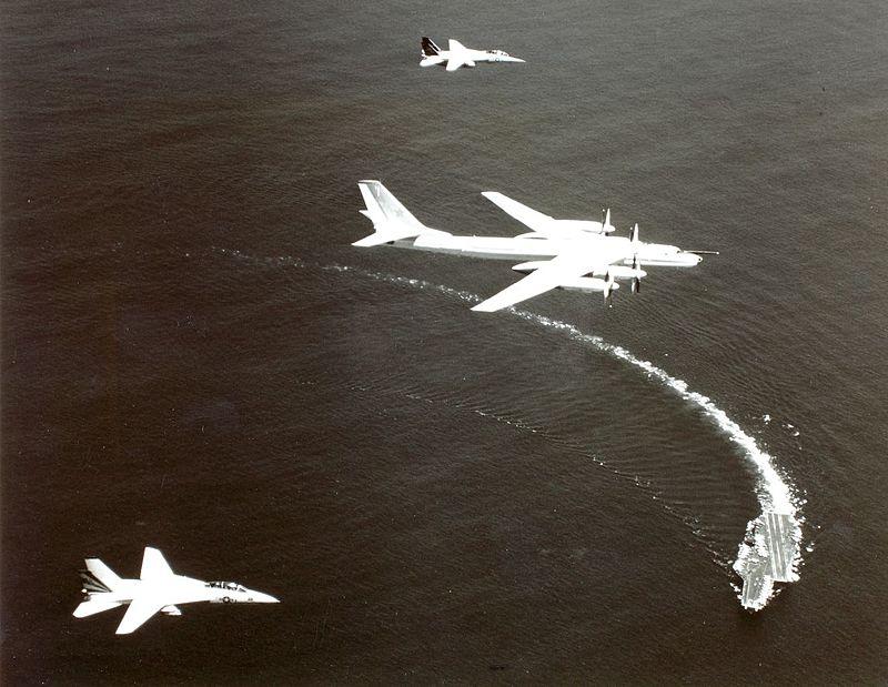 Американские истребители (Grumman F-14A) сопровождают Ту-95, а на заднем плане — авианосец («Kitty Hawk»)