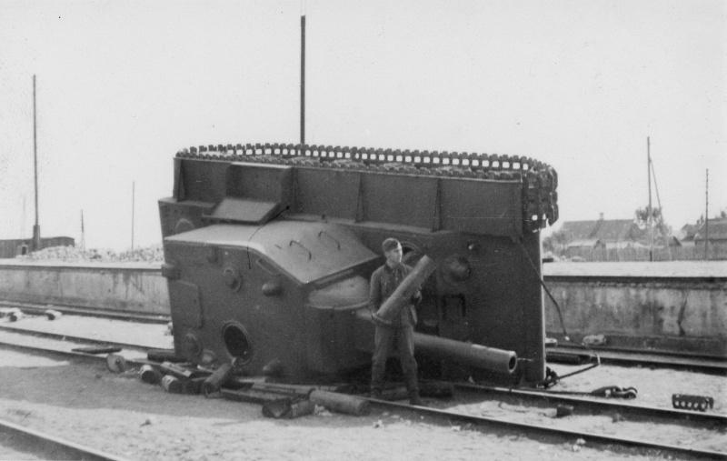 Немецкий солдат рядом с советским тяжелым танком КВ-2, опрокинувшимся с железнодорожной платформы на станции Лида