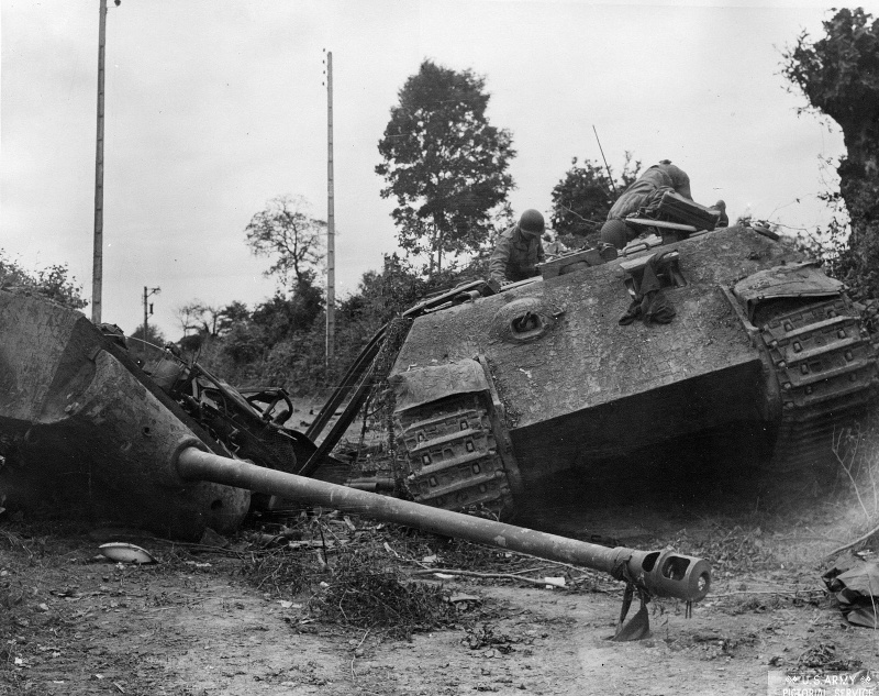 Два американских солдата осматривают немецкий танк «Пантера» с сорванной башней