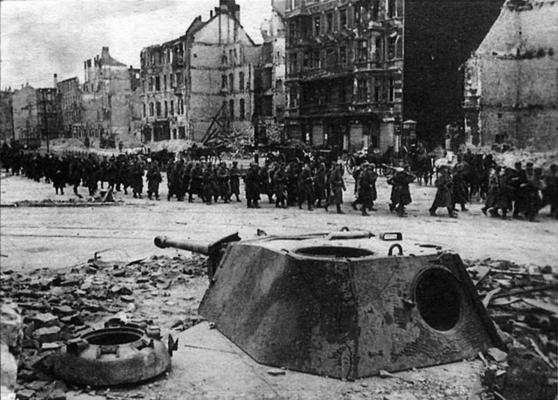 Колонна советских солдат проходит мимо башни от немецкого танка Pz.Kpfw. V «Пантера», установленной в качестве долговременной огневой точки (ДОТ) посреди улицы Берлина.