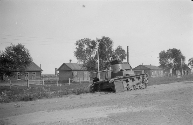 Советский легкий танк Т-26, брошенный на дороге в деревне из-за неисправности двигателя