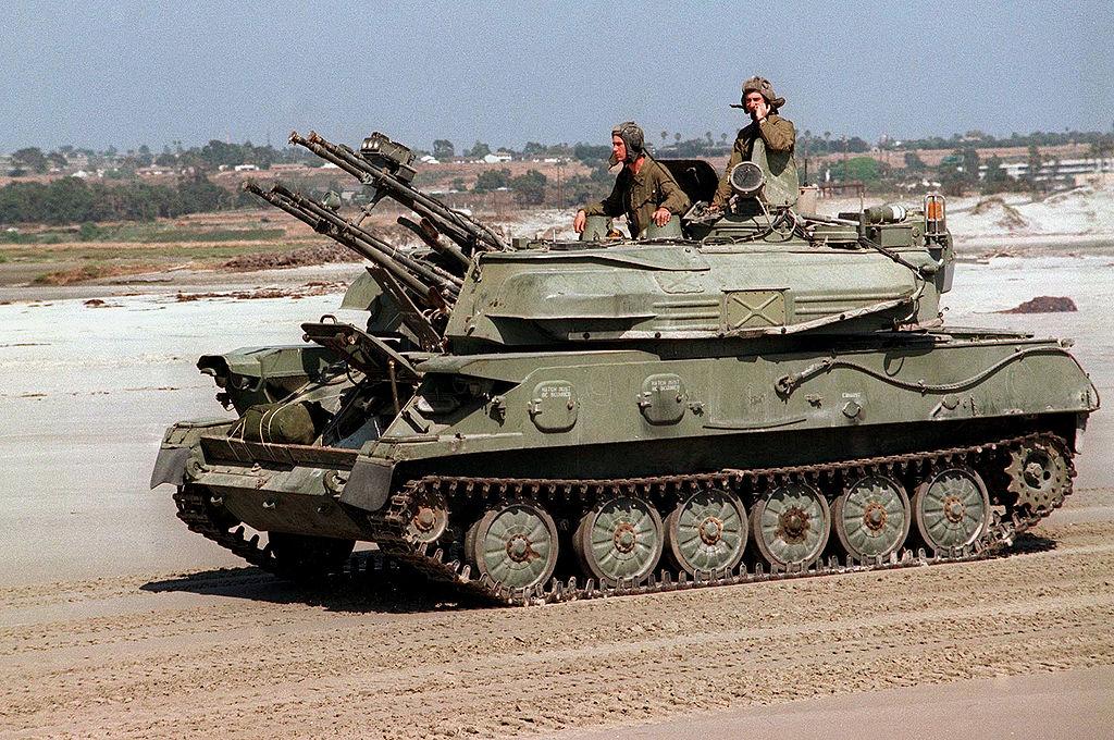ЗСУ-23-4 «Шилка» по-походному: стволы пушек закрыты заглушками, антенна локатора сложена, головки прицелов закрыты бронеколпаками. Ближе к нам — командир установки. Дальше от нас — либо наводчик, либо оператор дальности — у них общий люк, вероятнее, что наводчик, — его место располагается посредине между командиром и оператором дальности