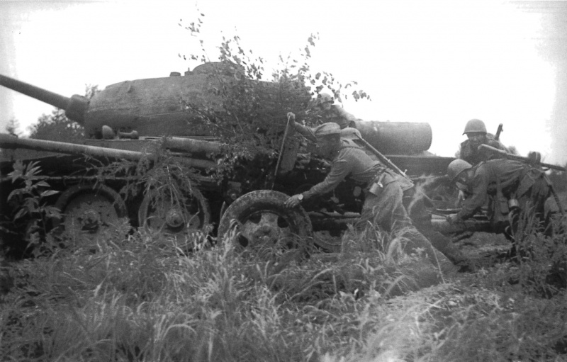 Расчет советской 76-мм пушки ЗиС-3 меняет позицию на Сахалине у танка Т-34-85.