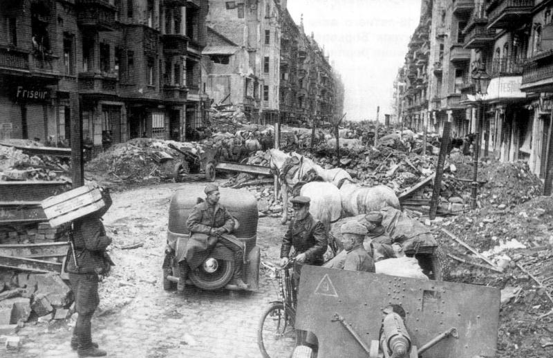 Советские солдаты в Берлине по окончанию боев. На переднем плане и позади, за автомобилем — орудия ЗиС-3 образца 1943 года.