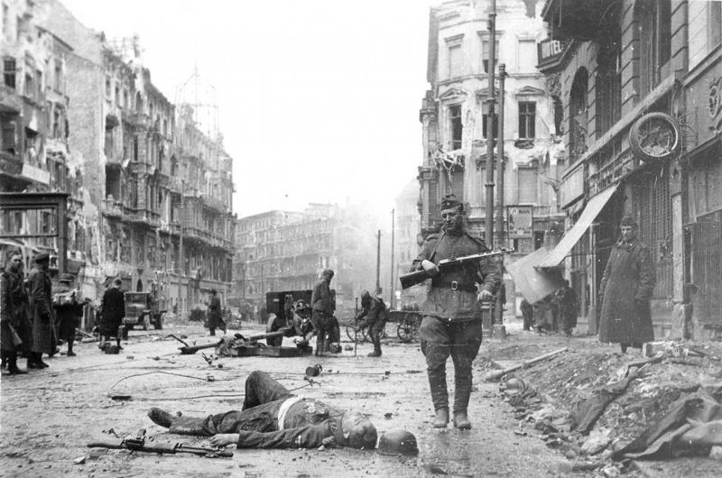 Советский солдат идет мимо убитого гауптштурмффюрера СС на улице Фридрихштрассе около станции метро «Ораниенбургер Тор» в Берлине. На заднем плане 76-мм дивизионная пушка ЗиС-3.