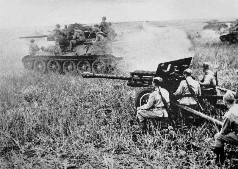 Советский танк Т-34 с десантом на броне проезжает рядом с 76,2-мм дивизионной пушкой ЗиС-3.