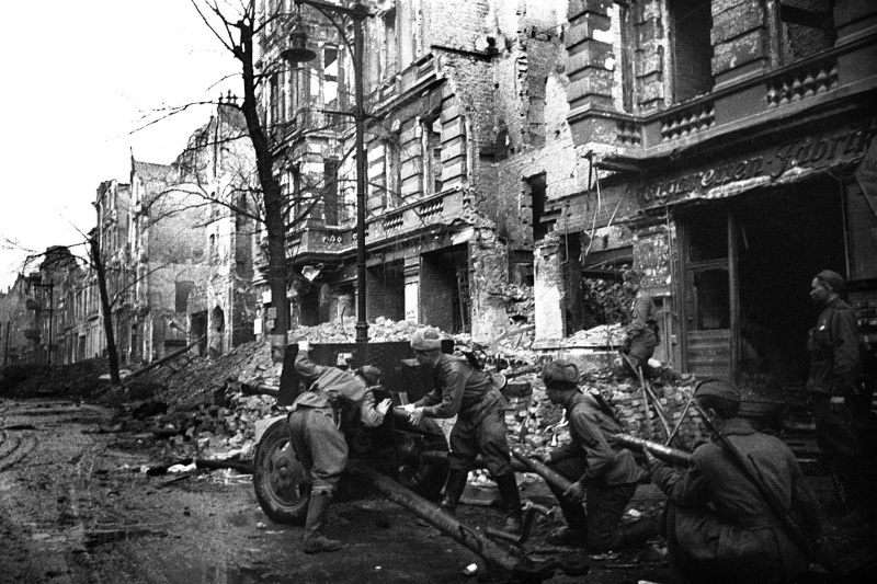 Расчет советской 76,2-мм пушки ЗиС-3 ведет огонь по гитлеровцам на улице Берлина.