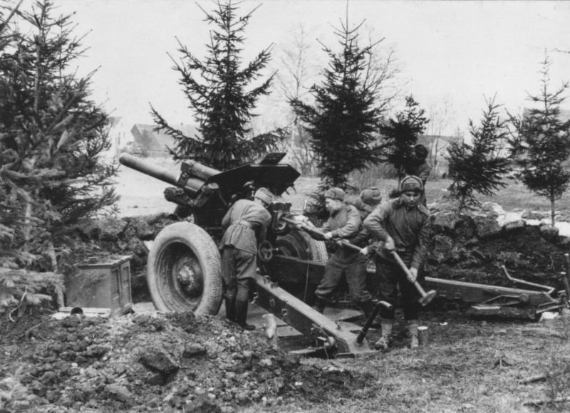Советский артиллерийский расчет занимается оборудованием окопа и подготовкой 122-мм гаубицы М-30 образца 1938 года к стрельбе.