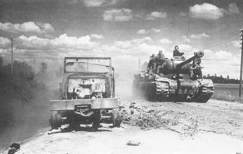 Танк ИС-2 с десантом на борту движется по Рижскому шоссе. На обочине дороги разбитый и сгоревший грузовик Studebaker US6.