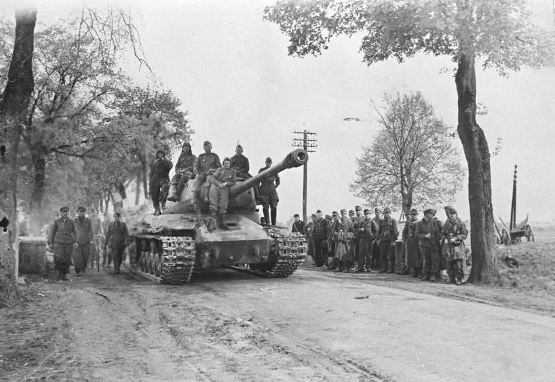 Советский тяжёлый танк ИС-2 на дороге у группы немецких военнопленных