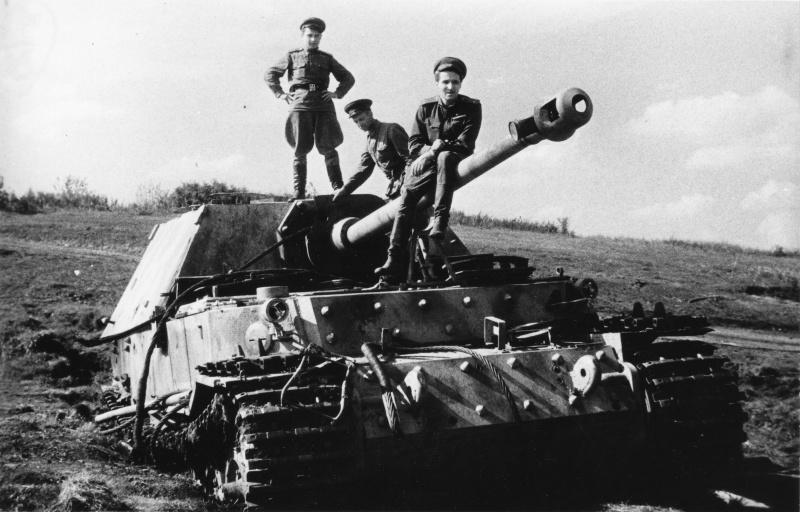 Фронтовой корреспондент Константин Михайлович Симонов (1915—1979) сидит на стволе орудия захваченной немецкой САУ «Фердинанд», подбитой на северном фасе Курской дуге