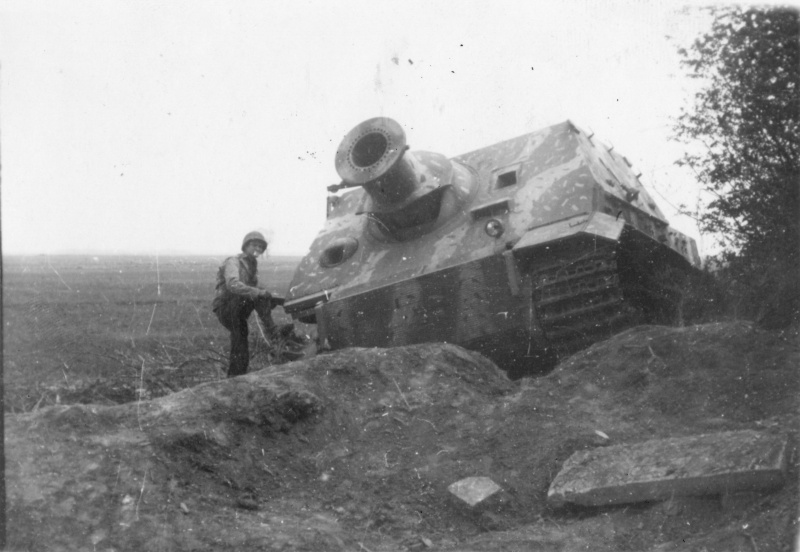 Солдат 5-й бронетанковой дивизии США осматривает немецкую САУ «Штурмтигр» (38 cm RW61 auf Sturmmörser Tiger), брошенную возле моста.