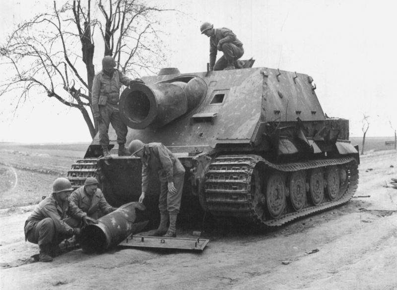 Военнослужащие 9-й армии США осматривают немецкую САУ «Штурмтигр» (Sturmtiger), захваченную в районе Миндена (Minden), Германия.