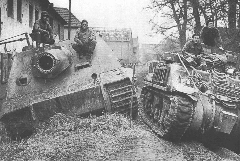 Британцы проезжают на бронированной ремонтно-эвакуационной машине M4 ARV (на базе танка M4 «Шерман») мимо тяжелой немецкой САУ «Штурмтигр», брошенной экипажем из-за поломки и захваченной американцами. Поселок Оберембт (Oberembt).