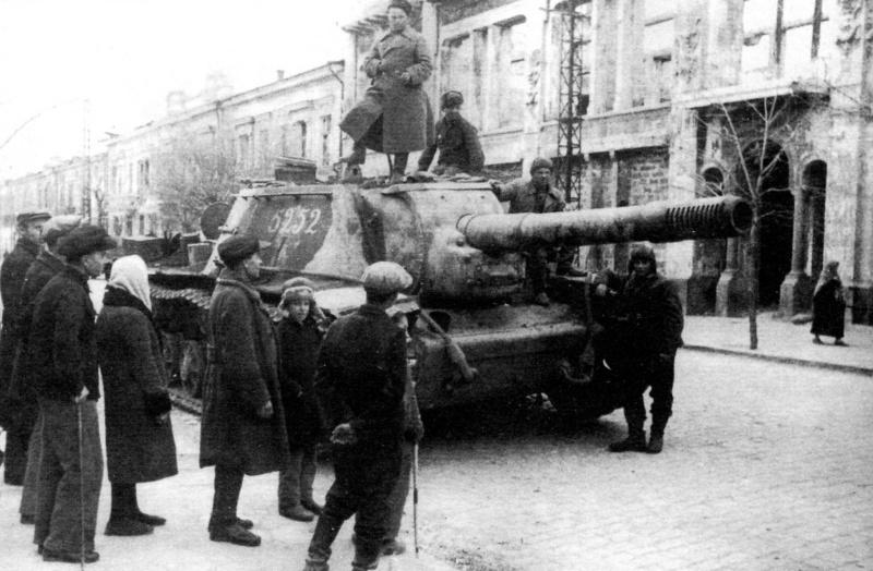САУ СУ-152 1452-го самоходно-артиллерийского полка РГК 2-й гвардейской армии 4-го Украинского фронта на фоне разрушенного здания швейной фабрики им. Крупской на улице Карла Маркса, д. №1 в Симферополе.