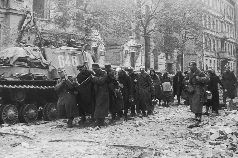 Немецкие военнопленные и жители Берлина с раненым, лежащим на одеяле, проходят по улице в центре Берлина мимо советской САУ ИСУ-152. В группе находятся также другие раненые, неспособные передвигаться в одиночку.