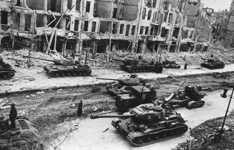 Бронетехника и артиллерия 1-го Белорусского фронта на улице Франкфуртер Аллее (Frankfurter Allee) в Берлине. В центре и слева танки Т-34-85, рядом тягач с 203-мм гаубицей Б-4 на прицепе. В кадре четыре тяжелых танка ИС-2, возле легковушки стоит САУ ИСУ-152.
