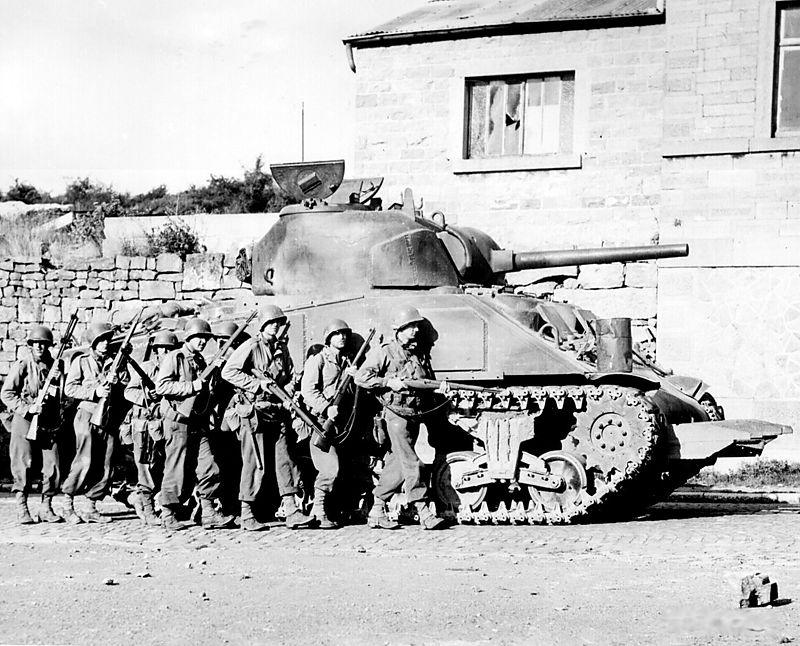Пехота под прикрытием танка «Шерман», оснащённого резаком для преодоления живых изгородей — бокажей