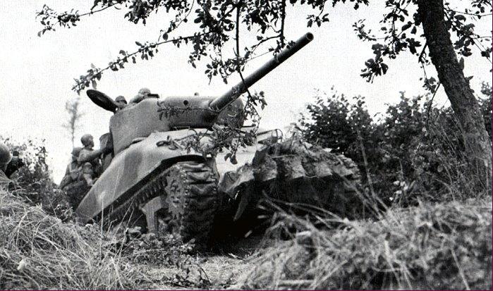 M4A1(76)W пробивается через «живую изгородь». Видны установленные на танк приспособления для прохода через кустарник.