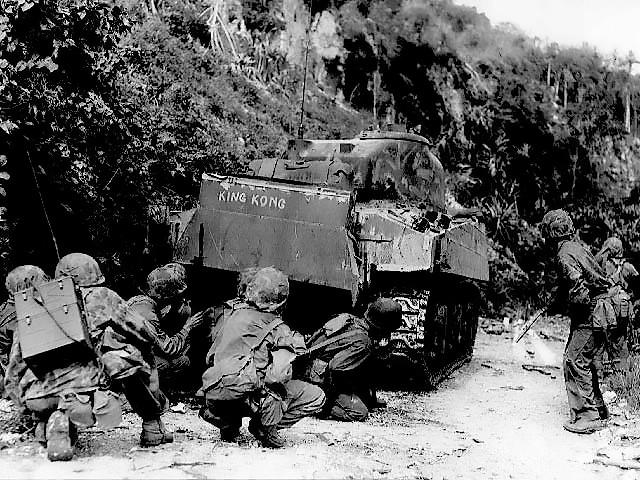 Морские пехотинцы укрываются за танком на Сайпане. Танк M4A2, с установленным шнорхелем для действий на мелководье
