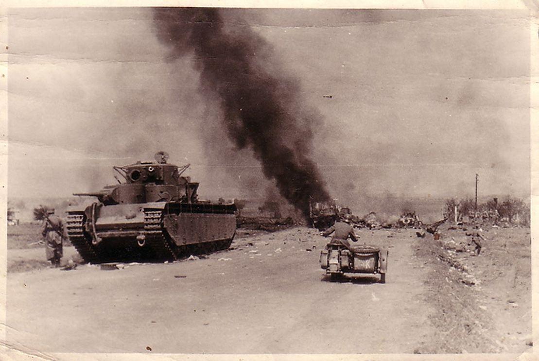 Подбитый танк Т-35 на фоне уничтоженной им немецкой колонны