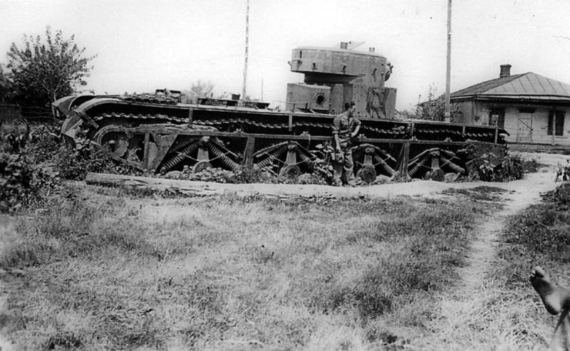 Немецкий военнослужащий фотографируется у советского танка Т-35, подбитого и брошенного в районе Григоровки