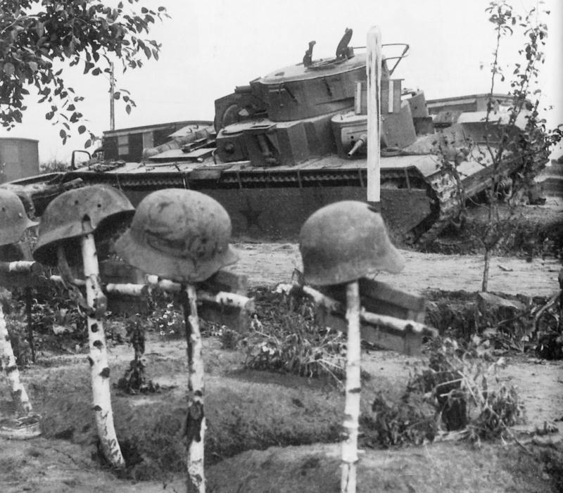 Могилы немецких солдат на фоне советского тяжелого танка Т-35, подбитого на трассе поселок Верба — поселок Птичье (Украина)