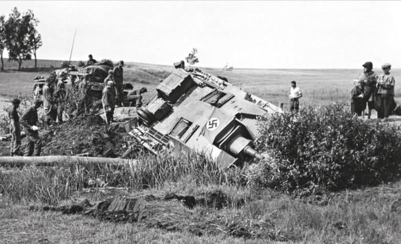 Солдаты вермахта у сошедшей с дороги и увязшей в кювете САУ StuG III Ausf. В. Машина выпущена фирмой Алкетт (Alkett) в июне 1940 г. – марте 1941 г.